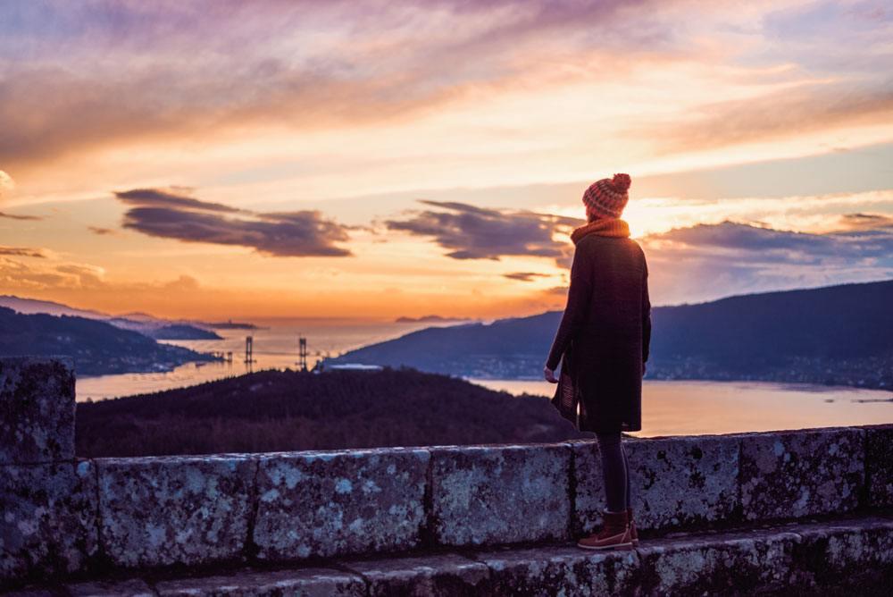 Una mujer observa un atardecer con una Ría de fondo, un puente y pueblos marineros. Lleva una chaqueta de punto y un gorro de lana.
