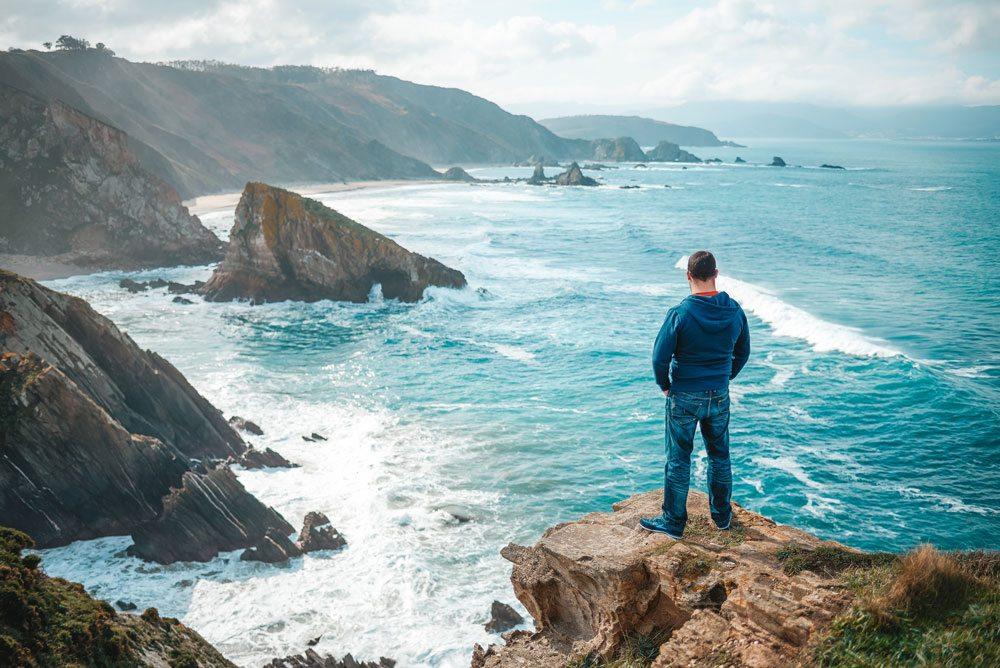 Un hombre vestido con una sudadera azul y vaqueros mira el paisaje en una playa gallega de pie sobre una roca con las manos el los bolsillos.