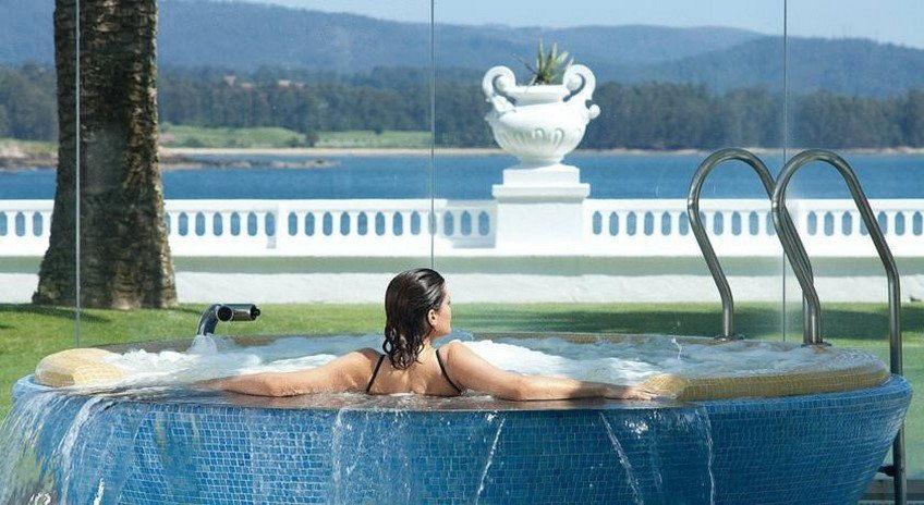 Una mujer se toma un baño en la piscina Jacuzzi del balneario de La Toja mientras observa las vistas de la ría al fondo.
